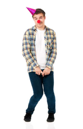 modest: Modest young man in shirt with red clown nose and birthday cap, isolated on white background Stock Photo