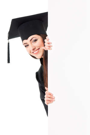 Beautiful graduate girl student in mantle showing blank placard board, isolated on white background