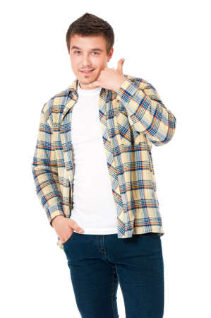 Young man in shirt making a call me gesture, isolated on white background photo