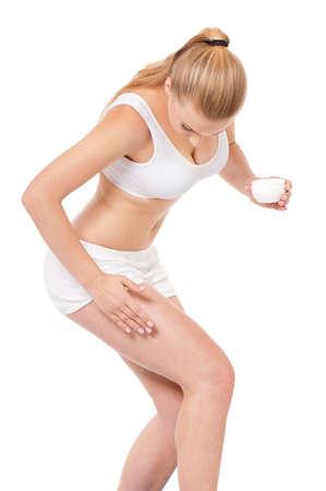 humidify: Woman applying moisturizer cream on legs, isolated on white background Stock Photo