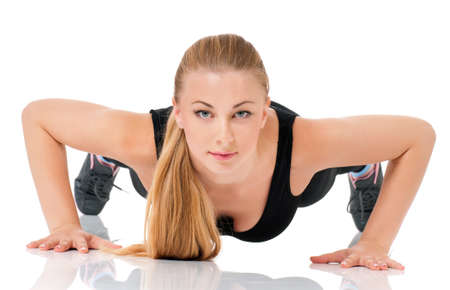 Young fitness woman doing push up, isolated on white background photo