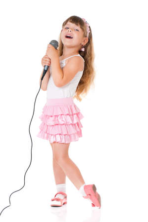 cantando: Niña hermosa con el micrófono aislado en el fondo blanco Foto de archivo