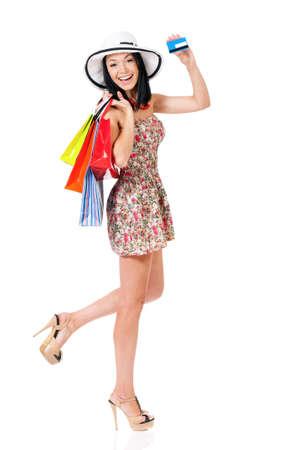 Compras mujer feliz y sonriente sosteniendo bolsas de compras que muestra la tarjeta de crédito o tarjeta de regalo, aisladas sobre fondo blanco