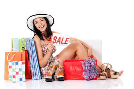 Shopaholic shopping woman with many shopping bags holding a signboard announcing a Sale, isolated on white background photo