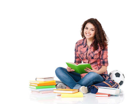 Beautiful student girl with books sitting on floor, isolated on white background photo