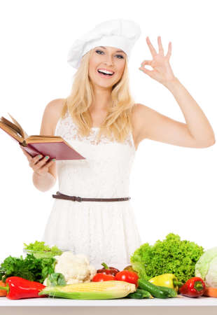 Woman in chef hat with fresh vegetables, isolated on white background photo