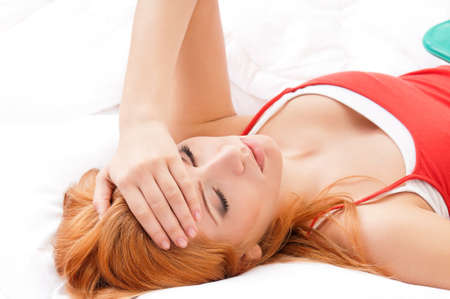 Woman with headache laying in bed at home photo