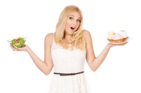 Beautiful woman choosing between fresh vegetables and cake  photo