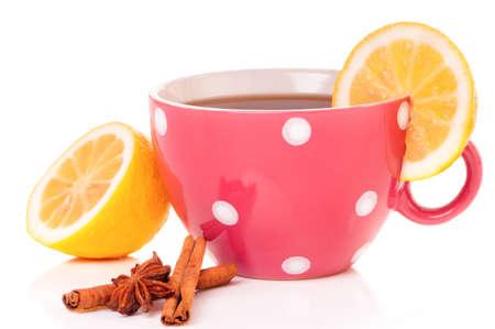 mugged: Big mug polka dot of tea with lemon and spices, isolated on white background