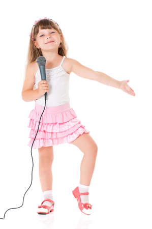 ni�o cantando: Ni�a hermosa con el micr�fono aislado en el fondo blanco Foto de archivo