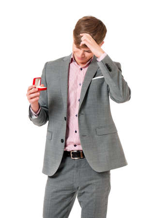 Young man a puzzled holding box with wedding ring, isolated on white background photo