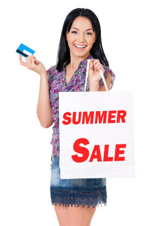 Portrait of young happy smiling woman with shopping bags showing credit card or gift card, isolated over white background photo