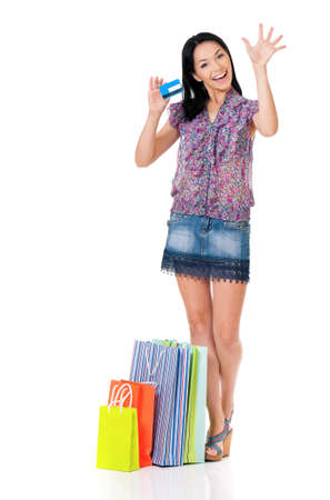 Beautiful young woman with shopping bags showing credit card or gift card, isolated over white background photo
