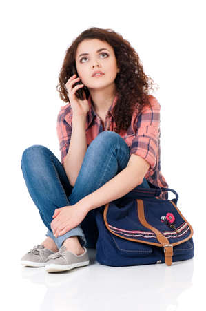 Student girl with bag sitting on floor and talking on cell phone photo