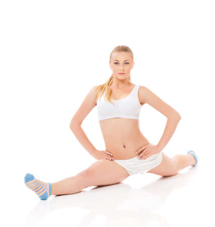 Beautiful young woman doing stretching exercise on the floor, isolated on white background photo