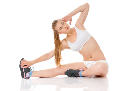 Beautiful young woman doing fitness exercise on the floor, isolated on white background photo