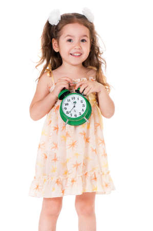 Happy little girl with green alarm clock, isolated on white background  photo