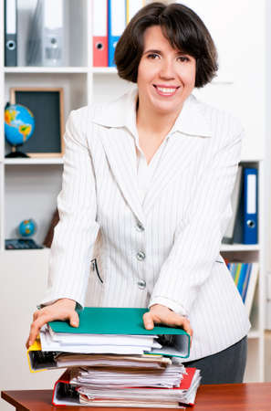 Portrait of successful business woman or teacher with folders at her office photo