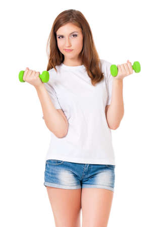 Teen girl with dumbbells working out, isolated on white background photo