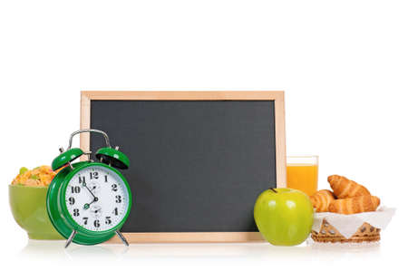 Big green alarm clock with breakfast and small chalk board, isolated on white background photo