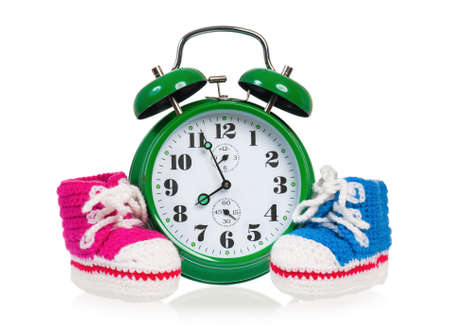 Green alarm clock with  baby boots, isolated on white background  photo