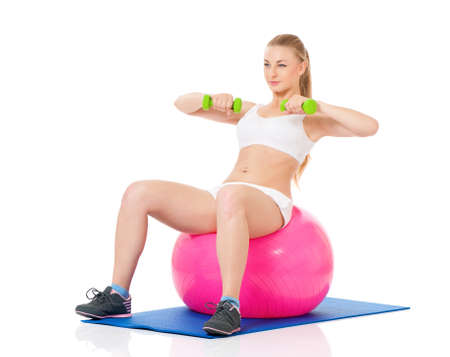 Young woman in fitness wear exercising with fitness-ball and dumbbells, isolated on white background photo