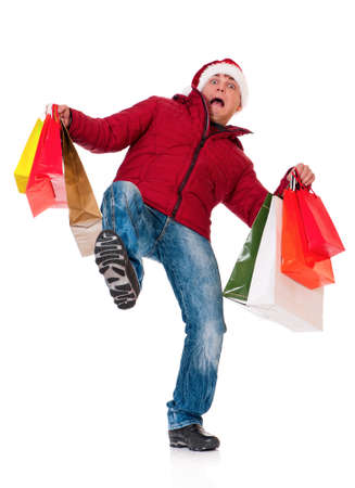 Full length portrait of a young man in winter clothing and Santa hat with shopping bags slipping on floor isolated on white background photo