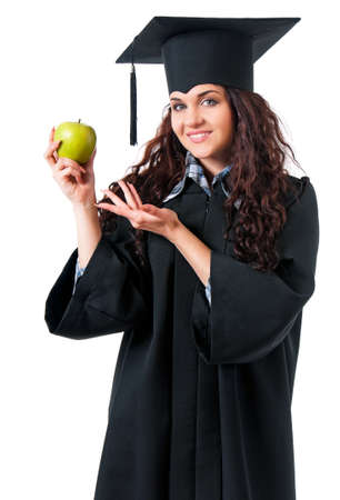 Beautiful graduate girl student in mantle with green apple, isolated on white background photo