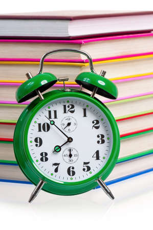Big green alarm clock with pile of books photo