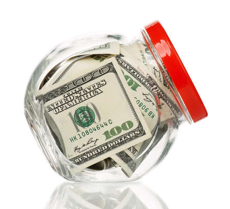 meanness: Many dollars in a glass jar isolated on white