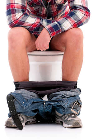 Man is sitting on the toilet bowl photo