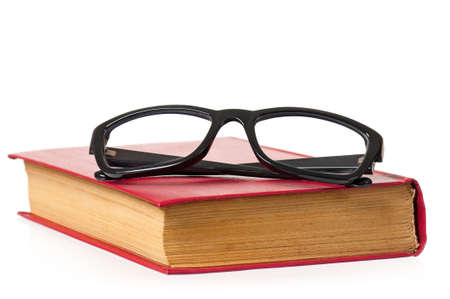 Black eye glasses and old book isolated on white background photo