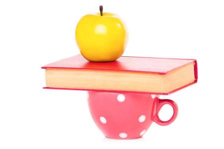 Big mug polka dot of tea and book, isolated on white background Stock Photo