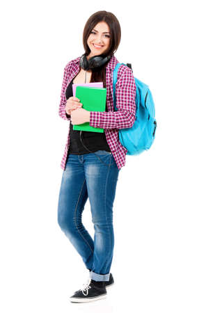 Beautiful student girl with backpack, black headphones and books, isolated on white background photo