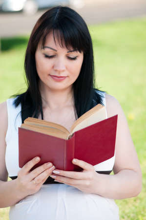 Happy pregnant woman with book in park outdoors photo