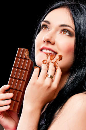 Beautiful young woman with black hair holding a chocolate bar photo