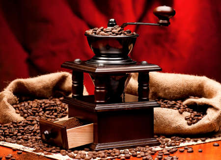 Manual coffee grinder with coffee beans on red background Stock Photo