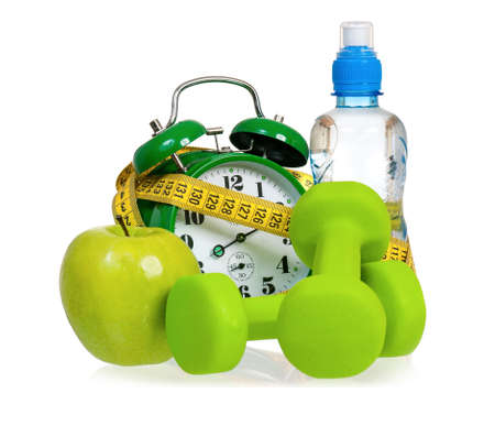 healthy lifestyles: Green alarm clock, apple, bottle of water,  measuring tape and dumbbells as concept of diet - isolated on white Stock Photo