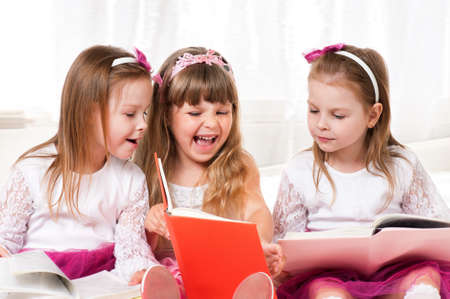 Three beautiful little girls reading book at home photo