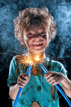 Portrait of little crazy electrician over black background Stock Photo