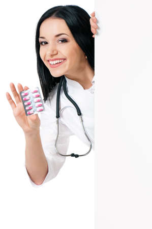 Female doctor holding a pills and clipboard, isolated on white  photo