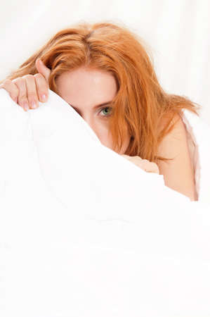 Woman is lying in bed under blanket and looking at camera photo