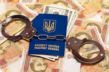 hryvna: International Ukrainian passport with US dollars and handcuffs on Hryvna banknotes