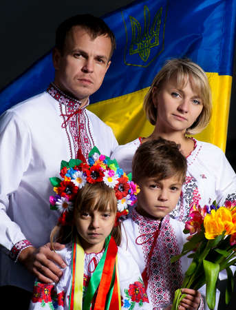 Proud family in the Ukrainian national costumes with Ukrainian flag photo
