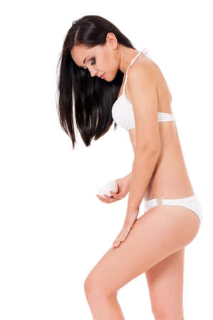 Female applying cosmetic cream from cellulite on the legs isolated on white  photo