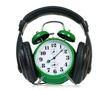 Green alarm clock with headphones, isolated on white background  photo