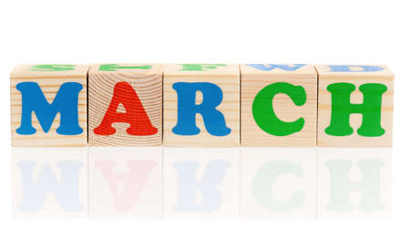 March word formed by wood alphabet blocks, isolated on white background  photo
