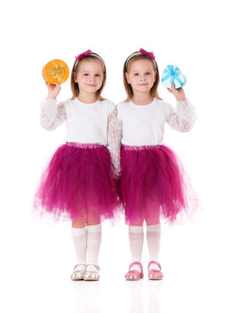 Portrait of two little girls twins with gifts, isolated on white background  photo