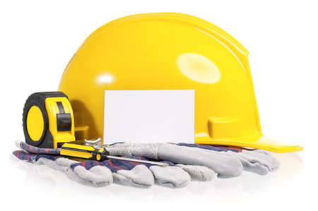 helmet safety: Yellow hard hat with work gloves and tools including screwdriver and a tape measure on a white background  Stock Photo