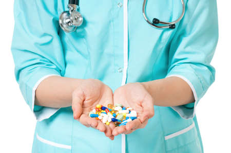 Cropped image of female doctor holding pills on white photo
